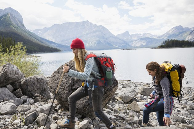 Female friends hiking with backpacks and hiking poles at craggy remote mountain lakeside