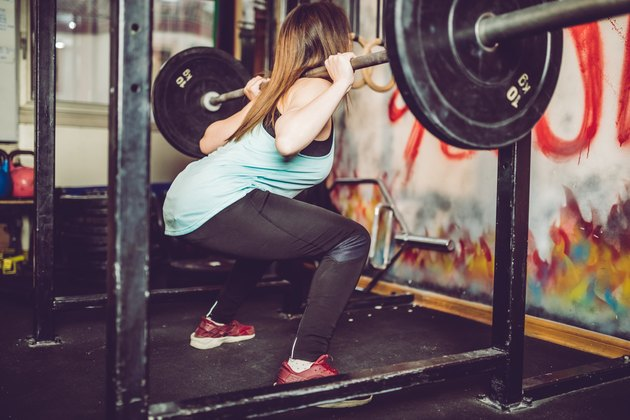 Young woman weightlifting in a gym to build muscle