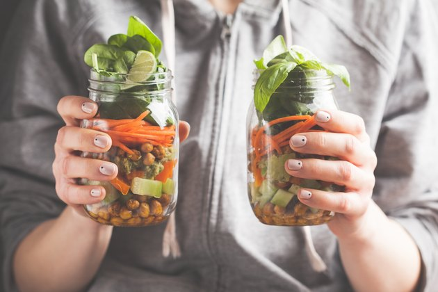 A woman holds and eats a salad in a glass jar with baked chickpeas, guacamole and vegetables. Healthy diet detox vegan food concept.
