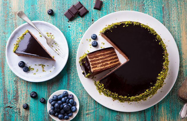 Chocolate cake on a white plate. Blue wooden background. Top view.