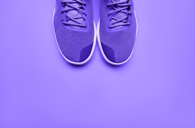 Purple running sneakers on a purple background for running for weight loss