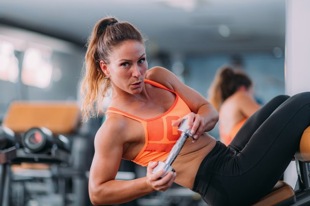 Female Athlete Doing Highly Effective Sit-Ups with Dumbbell