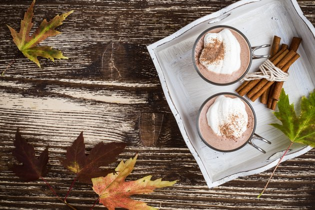 Homemade cinnamon and spice hot cocoa served with whipped cream. Thanksgiving table viewed from above