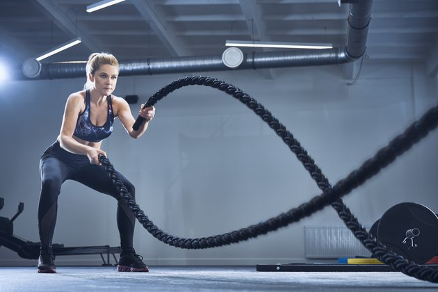 Athletic woman exercising with battle ropes at gym