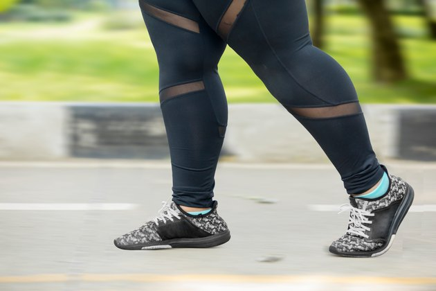 Woman's legs in black leggings on road