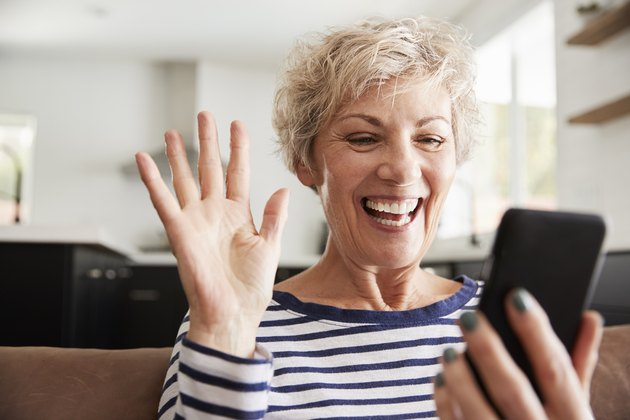 Senior woman video calling on smartphone at home, close up