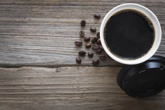 Overhead view of cup of coffee and coffee beans on wood