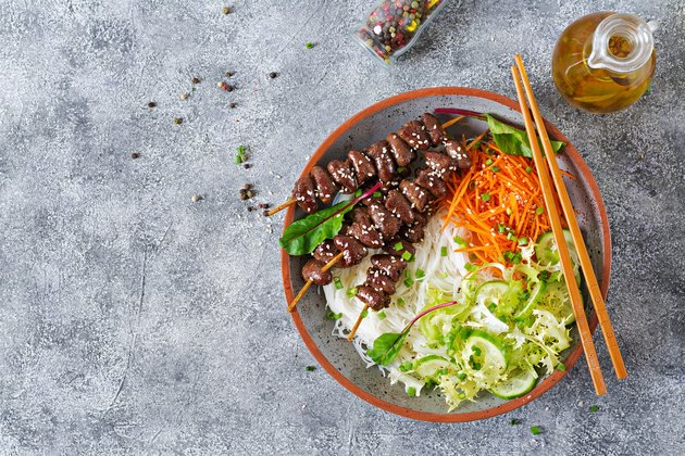 Chicken hearts in spicy sauce, rice noodles and vegetable salad. Healthy food. Top view