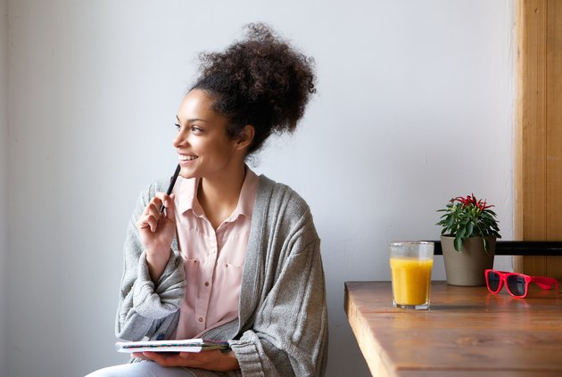 Happy young woman sitting at home with pen and paper