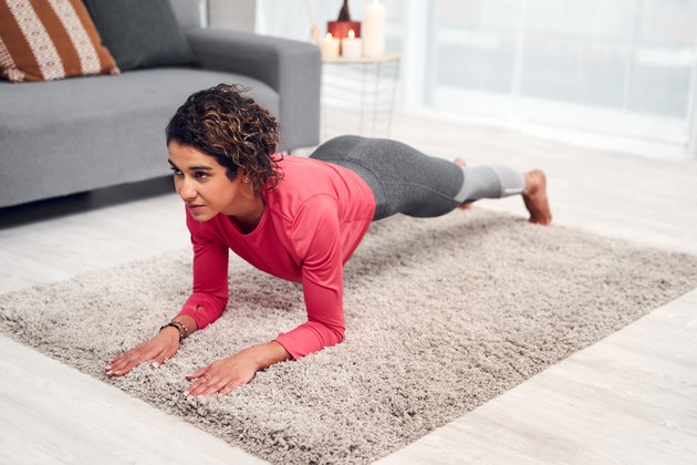 Woman doing a forearm plank exercise as part of a Pilates for beginners workout