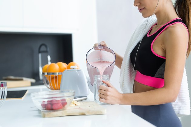 Sporty young woman serving strawberry protein shake in a glass jar in the kitchen at home.