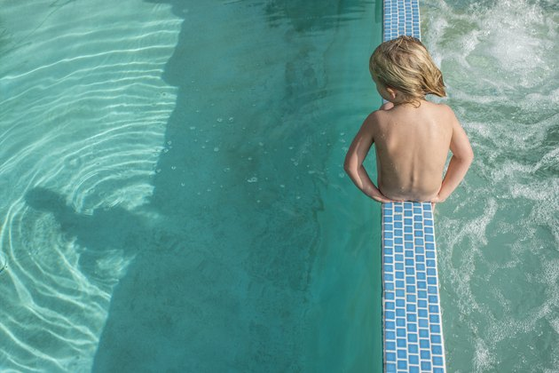 Boy sitting in between pool and hot tub