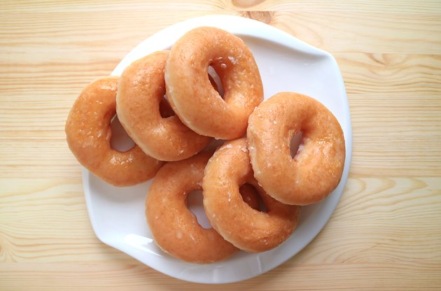 Top View of Sugar-glazed Doughnuts Served on White Plate on Wooden Table