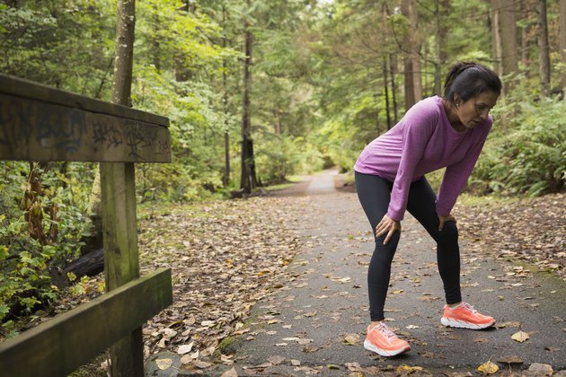Tired woman resting hands knees after run woods