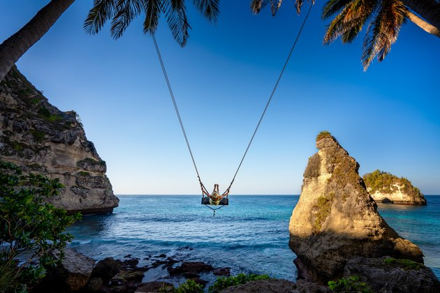 Young woman swinging at Nusa Penida, Indonesia.