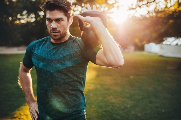 Fit young man exercising with kettlebell in park