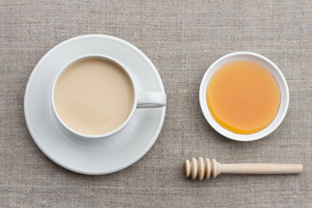 Spicy warming tea with milk in a white porcelain cup with honey and honey dipper