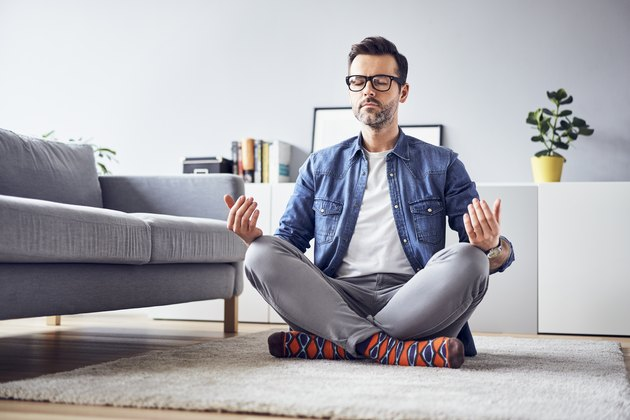 Relaxed man meditating at home in a cross-legged position