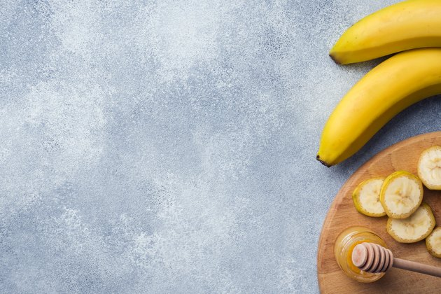 Banana and sliced banana into pieces with honey on textured background, copy space.