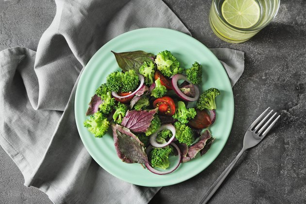 Plate with healthy vegetable salad on grey table