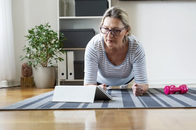 Senior woman following tutorial online and exercise at home during isolation for Covid - 19 at home