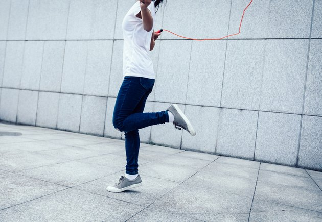 Young fitness woman rope skipping against city wall