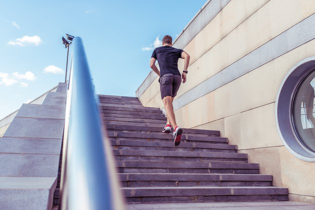 A male athlete runs in the morning jogging the steps, in the summer in the city sportswear t-shirt shorts sneakers, the background of the steps handrail, free space.