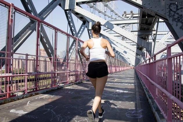 Young active woman running on Williamsburg Bridge