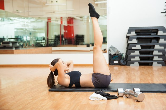 Cute girl raising her legs and doing crunches