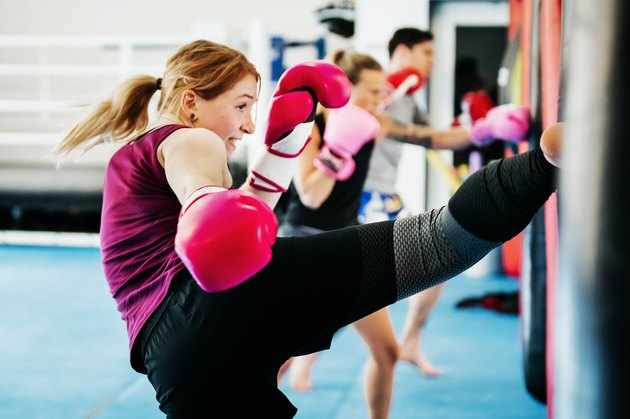 Women in a cardio kickboxing class at a gym for health benefits