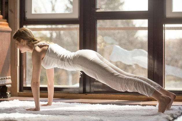 Young yogi attractive woman in Plank pose, home interior backgro