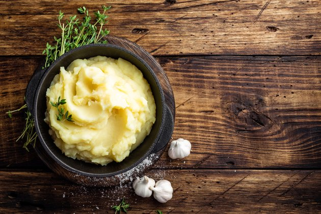 Mashed potatoes, boiled puree in cast iron pot on dark wooden rustic background, top view