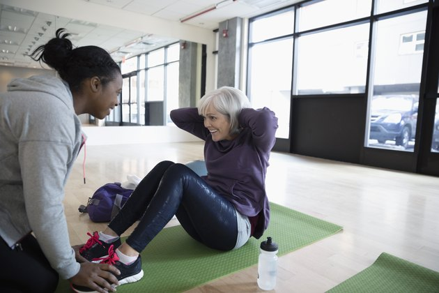 Personal trainer encouraging woman doing beginner HIIT workout at the gym