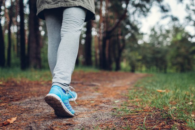 Woman tourist walking in spring forest. Close up of shoes. Traveling and tourism concept