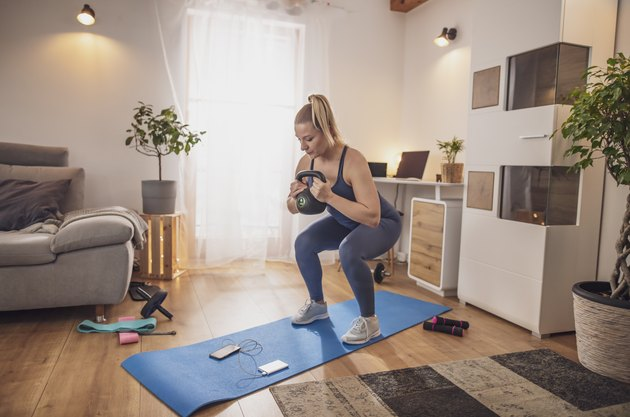 Young woman squatting with kettlebell on yoga mat in living room