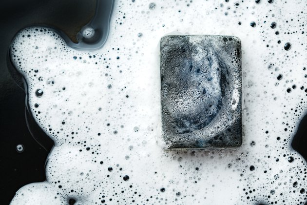 Black coal bar of soap in foam on dark