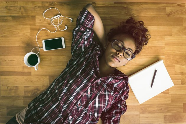 woman relaxing on floor taking a break from working doing box breathing