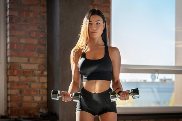 Attractive sporty girl doing exercise with dumbbells