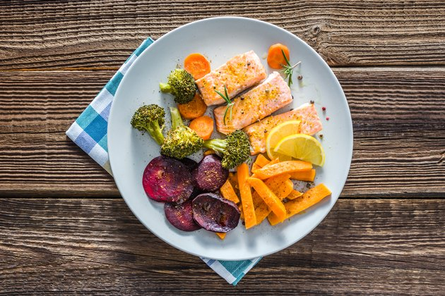 Appetizing diet food with grilled salmon and vegetable. Dinner on plate with fish fillet and cooked vegetables.