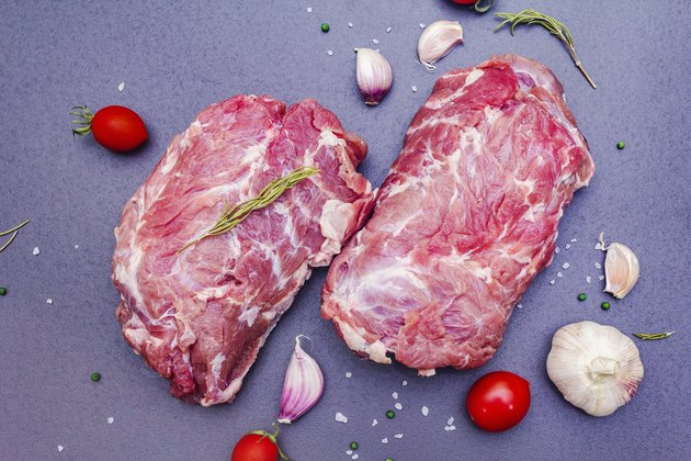 Raw beef meat. Animal protein with dry spiced, rosemary, garlic clove, sea salt and tomato cherry