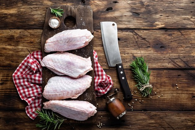 Raw turkey wings on wooden background top view, copy space, flat lay