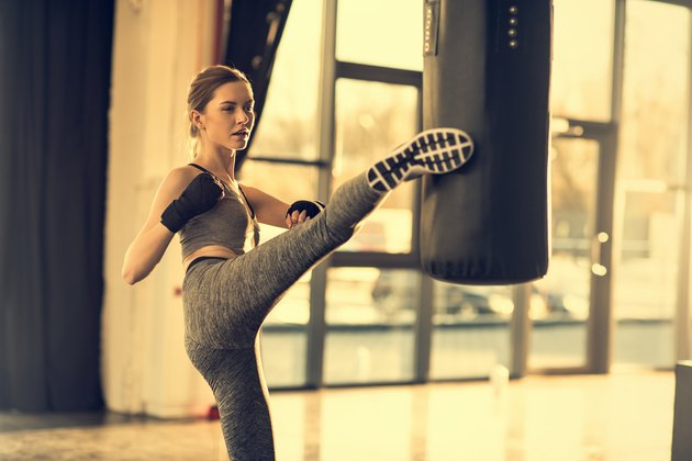 young sportswoman kicking punching bag in sports center