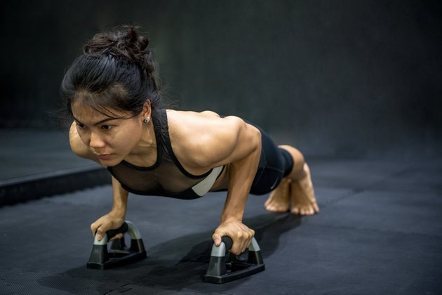 Young Asian athlete woman doing push up with push-up bars on the floor
