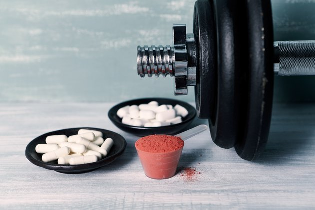 Creatine Powder, Aginine capsules, BCAA (amino acids) and a dumbbell in background. Sport nutrition. Wooden background. Close up.