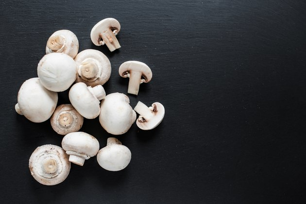 Fresh Mushroom champignon on dark   background, sliced and whole with copy space, ready for cooking
