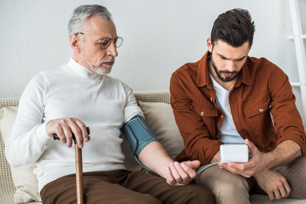 bearded man measuring blood pressure of senior father because he takes Lisinopril
