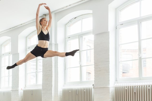 Ballerina doing the splits in mid-air at studio