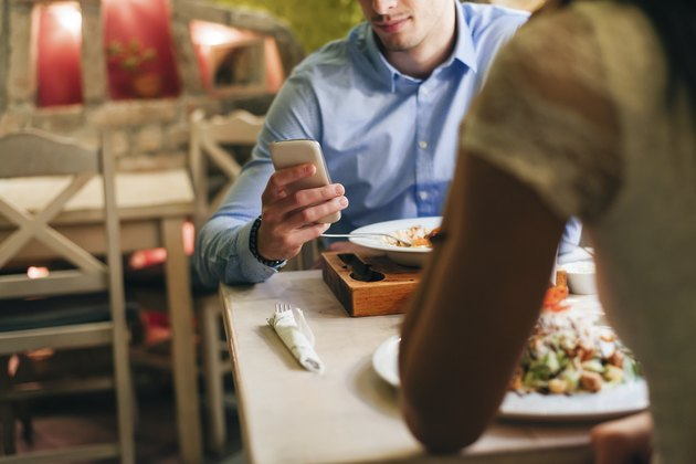 Man checking phone while having dinner in a restaurant