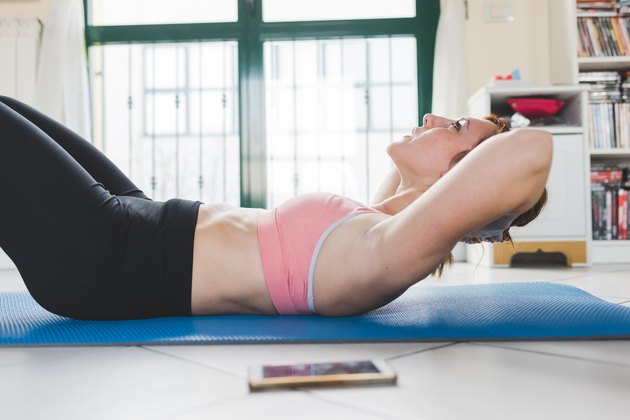 Young woman doing sit ups on yoga mat