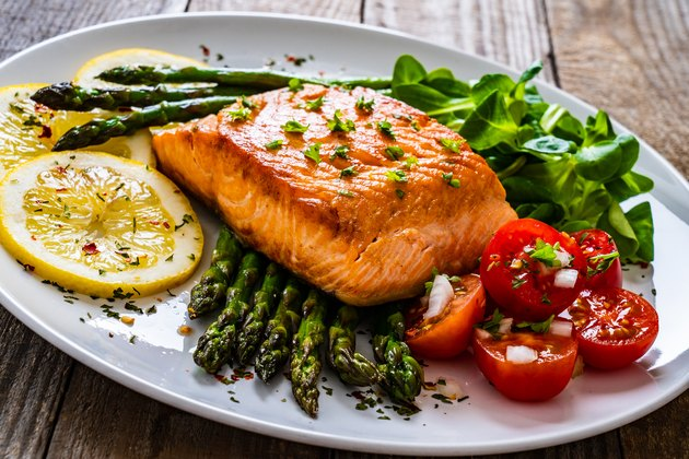 cooked salmon steak and asparagus on wooden table